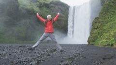 Girl jumping happy excited by waterfall on Iceland - tourist by Skogafoss - stock footage