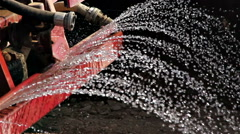 Water truck sprays water on a fresh layer of soil and rock Stock Footage