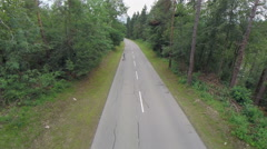 Skater on longboard riding towards aerial camera on empty road Stock Footage