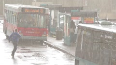 Bus Station Busy Rainy Wet Day Headlights On Rain Soaked People Waiting - stock footage