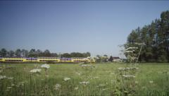 Springday with green fields and train in countryside Stock Footage