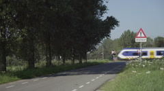 Dutch Railways train crossing the road Stock Footage