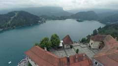 Flying above Bled lake uncover old castle high above - stock footage