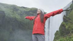 Happy woman by waterfall Skogafoss on Iceland - serene and free girl - stock footage