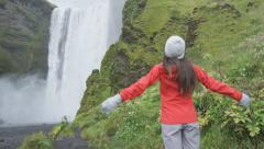 Waterfall - Happy woman by Skogafoss on Iceland serene and free Stock Footage