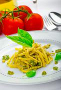 Italian pasta with basil pesto, late harvest wine Stock Photos