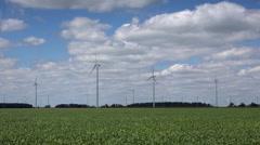Windmills generating green energy in farm field - stock footage