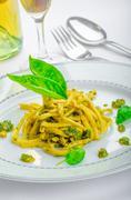Italian pasta with basil pesto, late harvest wine Stock Photos