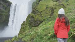 Waterfall - Tourist woman by Skogafoss on Iceland visiting famous landmarks Stock Footage