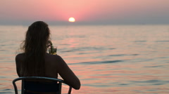 Woman with cocktail enjoying sunset on the shore Stock Footage