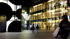 Customers walk between shopping buildings at night Stock Footage