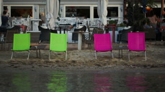 Four empty chaise-lounges on the beach with cafe behind Stock Footage