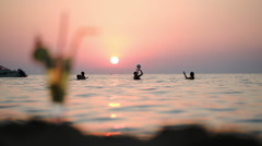 People in sea and cocktail on beach at sunset Stock Footage