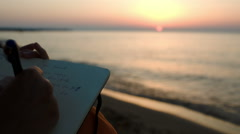 Woman making notes sitting by sea at sunset Stock Footage