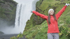 Blissful woman by waterfall Skogafoss joyful happy in bliss and joy Stock Footage