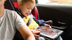 Happy boy playing game on pad during car travel Stock Footage