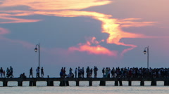 Timelapse of people walking on pier at sunset - stock footage
