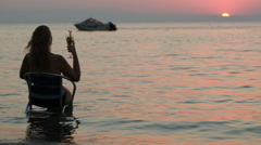 Woman with cocktail sitting on chair in sea Stock Footage