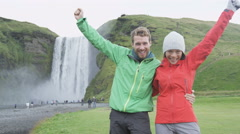People cheering by Skogafoss waterfall on Iceland - Happy couple excited Stock Footage