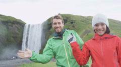 People waving hello hand by waterfall on Iceland - Happy couple saying hi Stock Footage