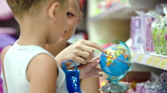Mother and son with small globe in the shop Stock Footage