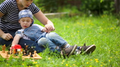 Mother and son spending time on the lawn in countryside Stock Footage