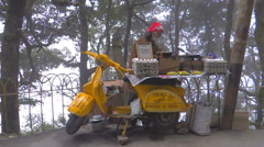 Mobile fast food shop on a two wheelerscooter Stock Footage