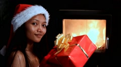 Mrs. Claus throw Christmas gift to fire in the stove Stock Footage