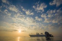 Small white motor boat anchored at near tropical island beach on sunset Stock Photos