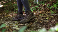 Low angle shot with boots hiking on leaves in the forest - stock footage