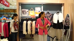Young women buying clothes at the mall, in China Stock Footage