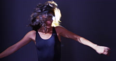 Stock Video Footage of Argentinian woman dancing and flipping hair in front of light