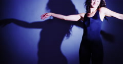 Woman dancing with shadow on wall Stock Footage