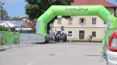 Stock Video Footage of First bicycle competitor arrive through finish line