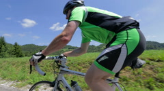Following cyclist uphill low angle Stock Footage