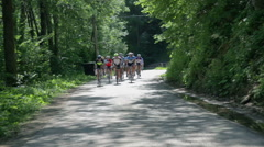 Group of cyclist on forest asphalt Stock Footage