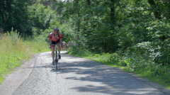 Bicyclist on forest road Stock Footage