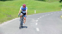 Cyclist speeding down the hill on a sunny day Stock Footage