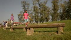 Three young girls passes wooden beam in the park. Stock Footage