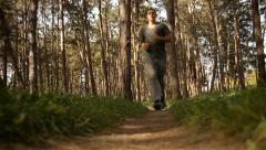 Male runner. Boy running through the forest. Guy jogging. Recreation race. - stock footage