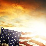 Stock Photo of american flag in front of bright sky