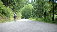 Bicyclist driving through big forest Stock Footage