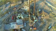 Trucks and excavator parked near former asphalt-concrete plant Stock Footage