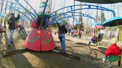 Fathers rotate carousel with kids at sunny spring day. Stock Footage
