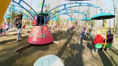 Man rotates carousel with children at sunny spring day. Stock Footage
