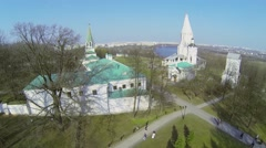 Tourists walk by alleys in museum preserve Kolomenskoe with Church Stock Footage