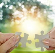 Fingers holding two puzzle pieces Stock Photos