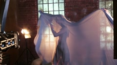 Shooting video clip with young cute girl and a veil in studio Stock Footage