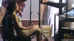 Stylist doing make-up to E.Vershanskaya before shooting clip Stock Footage