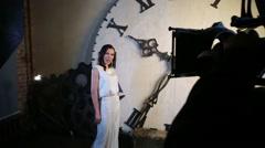 Beautiful brunette woman in dress sing near big clock at studio Stock Footage